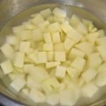 Pelamos las patatas, las cortamos en dados y las dejamos en agua para que desprendan parte del almidón mientras preparamos el resto de la receta.